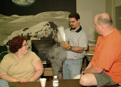 Candid photo of Dr. Christopher Palma demonstrating a model for a comet nucleus.