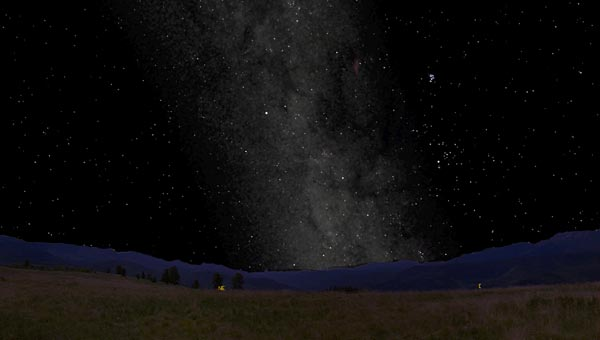 Image that shows the Milky Way as a patchy band of faint light stretching across the entire sky.