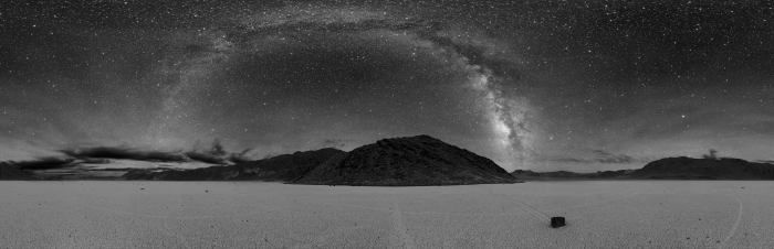 "Photograph of Death Valley showing a panorama of the entire sky, which includes an arc of glowing light, which is the band of star light we call ""The Milky Way""."