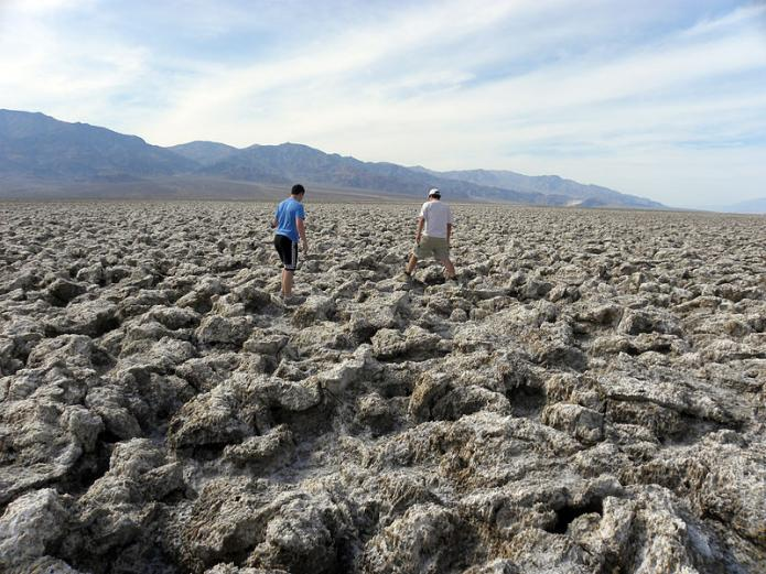 People walking on the rough surface of evaporite mineral halite (NaCL) formed in Death Valley, California