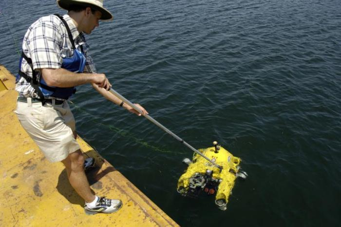 Man submercing an Automated Underwater Vehicle (AUV) in the water