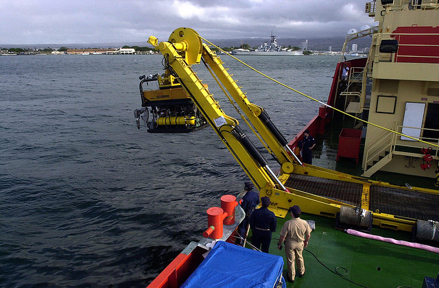 Three men on a deck or pier watching a Remotely Operated Vehicle (ROV) being used on the water