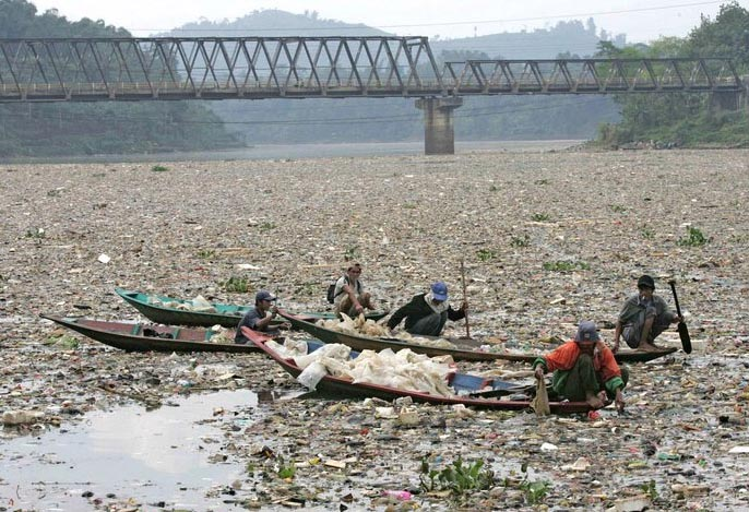 Men in boats in a heavily polluted river in China