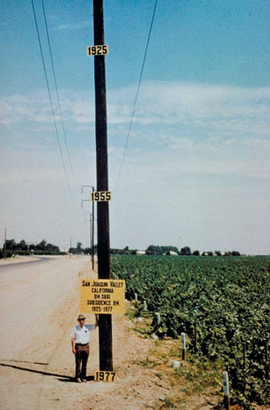 A man standing by a pole that marks the amount of land subsidence in the San Joaquin Valley as a result of overpumping for irrigation