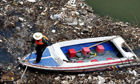 A man standing on a boat in a lake full of trash.