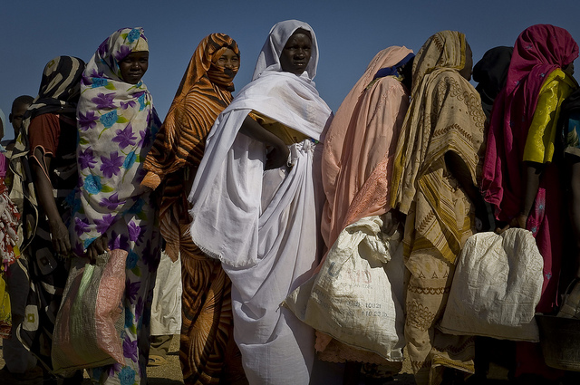Refugee women standing in food line.