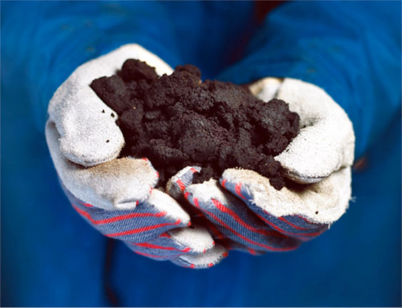 Gloved hands holding oil and tar sands.