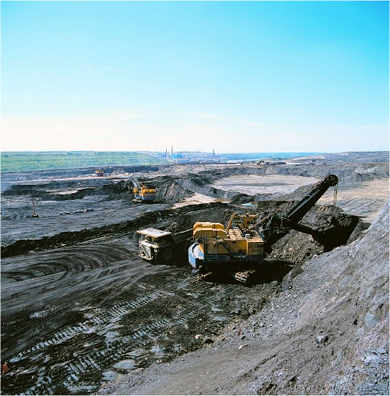 Heavy machinery mining in tar sands -  open pit mining.