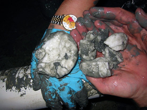 Hands holding clumps of gas hydrate, white but covered with wet sand.