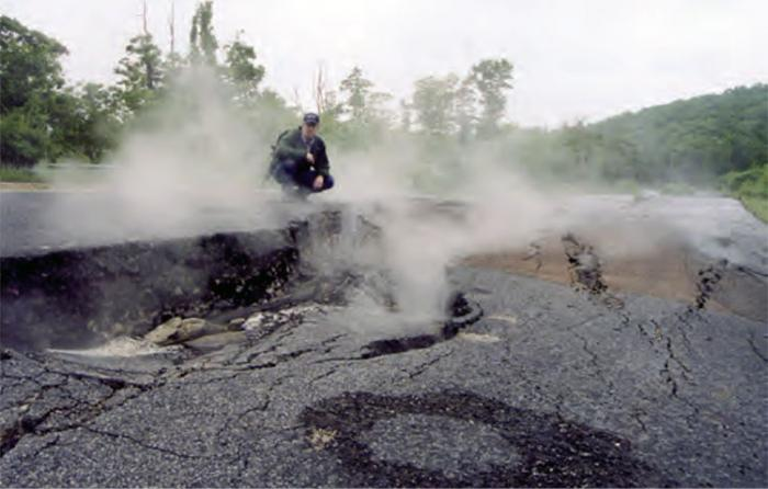 Person sitting on asphalt with big cracks in it watching the gases from an underground coal fire rising from the Earth's surface.