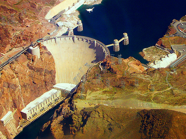 Hoover Dam. Big concrete wall separating the river. Water behind dam is higher elevation and much wider than the river below the dam