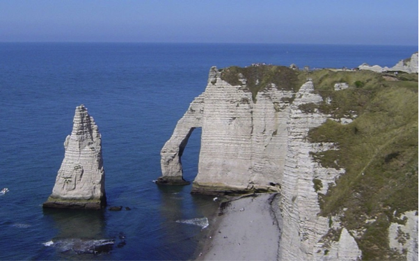 Cliff lined coast along northwestern coast of France with sea stack in foreground and sea arch in background.