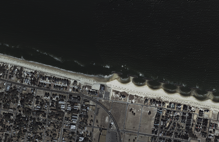 image of offshore breakwaters and tombolos. Looks like a wave made from the beach with half-moon areas for the water