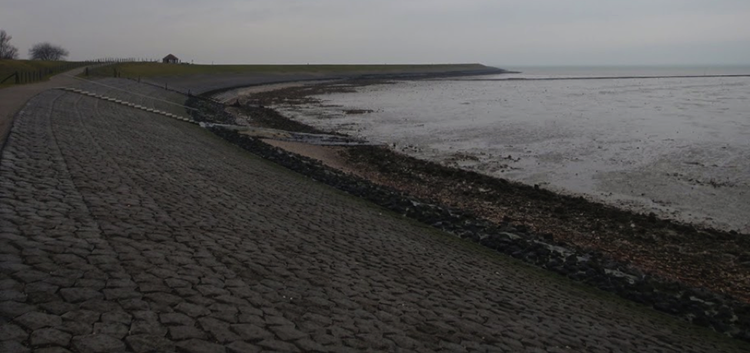Armored sea dike in the Netherlands at low tide slope made out of stones.