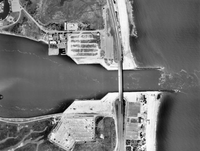 Arial image of Jetties at India River Inlet, DE with updrift accretion and downdrift erosion.