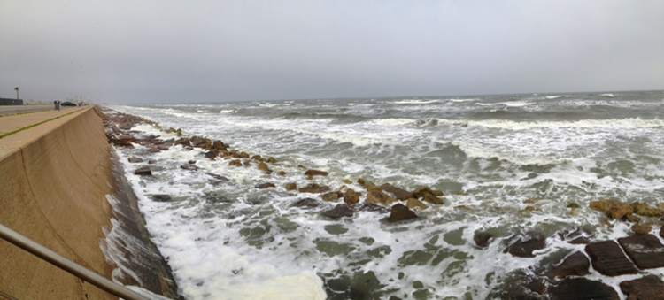 Waves breaking on the Galveston seawall. line of stones before the seawall