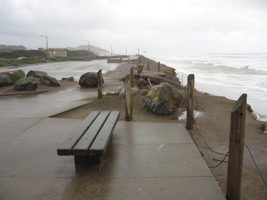 A bench Ocean Beach before after severe erosion. Bench on concrete platform with several feet of ground beyond the platform to the sea