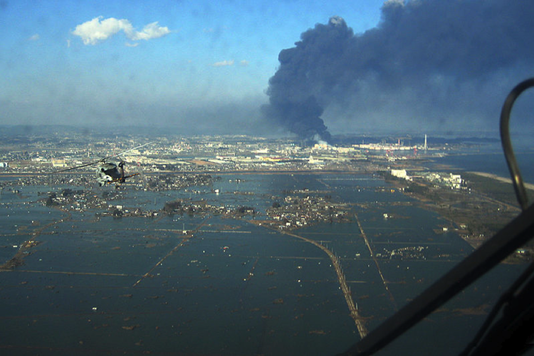 Sendai, Japan after Tohoku earthquake and tsunami, parts of city underwater and oil refinery billowing black smoke.