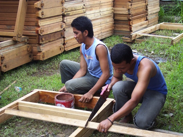 Indonesian students with wood and saw working on a project.