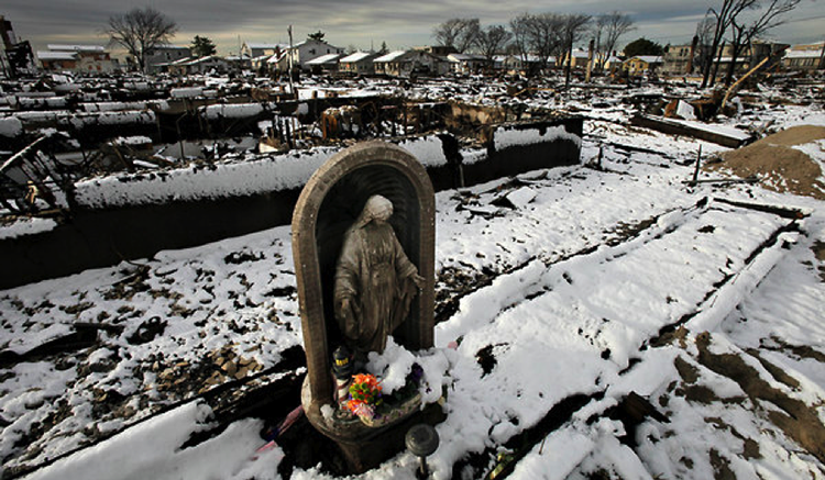 A statue of Virgin Mary surounded by snow and debris.
