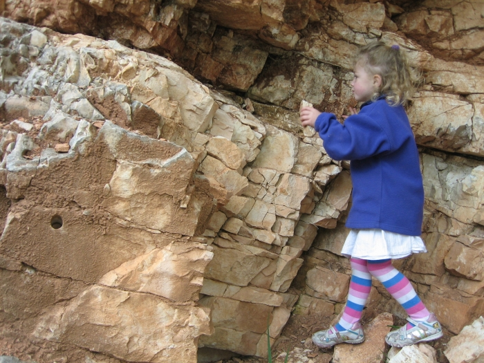 small girl playing with loose rocks at the K/T boundary