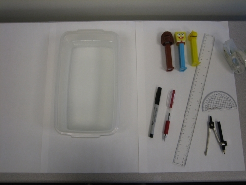 clear container, ruler, compass, protractor, 3 pez dispensers on a table