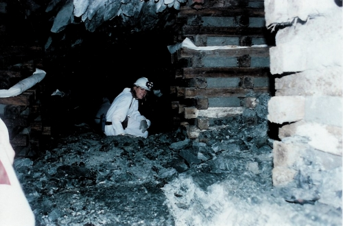 Eliza wearing white coveralls and a headlamp inside a gold mine