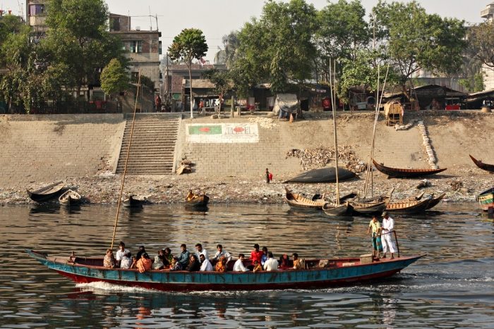 Bangladesh.  Boat on a river with some buildings on the bank