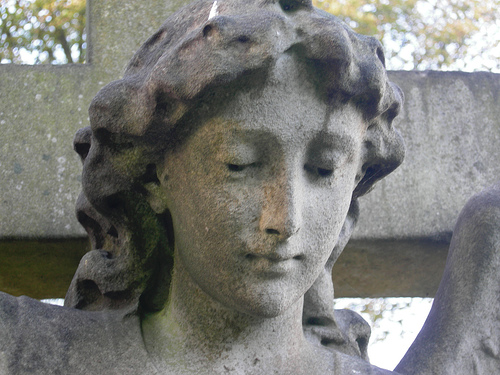 Picture of acid rain stone erosion to statue. Statue's face has discoloration and is splotchy.