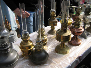 Many kerosene lamps on a table of varying shapes and sizes