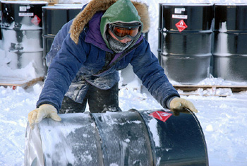 Colored picture of a man moving a barrel in the Alaskan oil fields