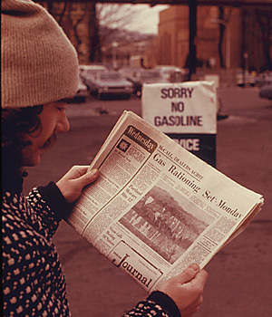 Someone reading a newspaper with the headline: Gas Rationaing Set: Monday