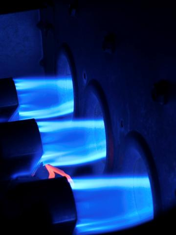 Burners in a boiler, blue flames pictured