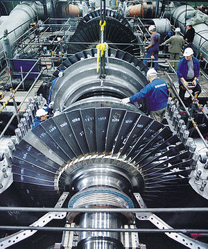 technicians installing large turbine in power plant
