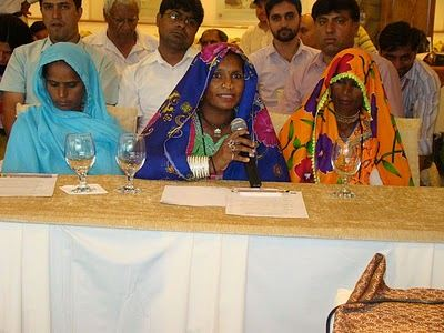 Hindi women sitting at a table. One of the women is talking into a microphone.