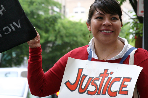 Woman with justice sign around neck and another sign with illegible words in her hand