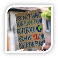 "a protester's sign which reads, ""Ask not what your planet can do for you, ask what you can do for your planet"""