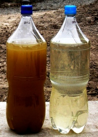bottles containing wastewater before (dark brown) and after treatment(clearish yelow)