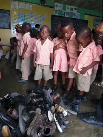example of re-distribution programs. pile of shoes surrounded by orphanage children