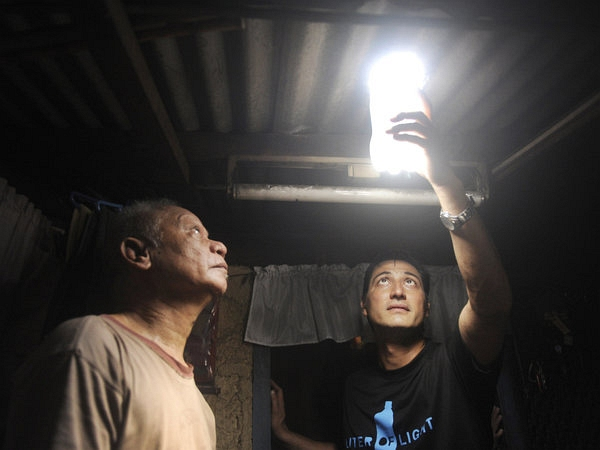 A man inspects a solar light bulb made from a discarded plastic soda bottle.
