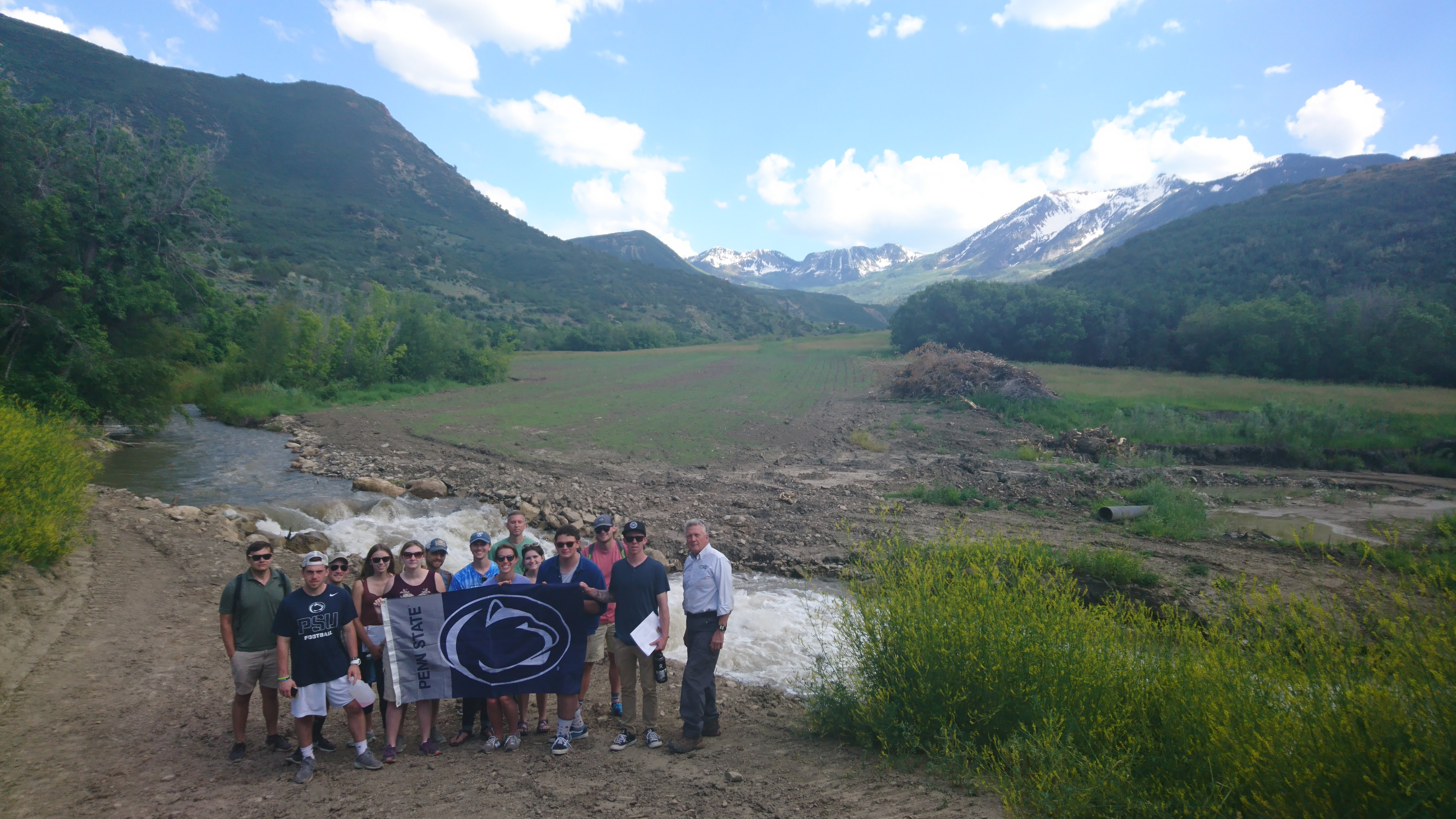 A group of Penn State students standing in front of mountain scenery with a Penn State flag