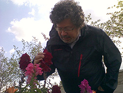 Image of Dr. Semih Eser looking at flowers