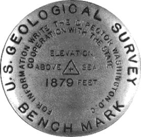 "A metal ""benchmark"" used to mark a location, shows elevation above sea level at +1879 feet."