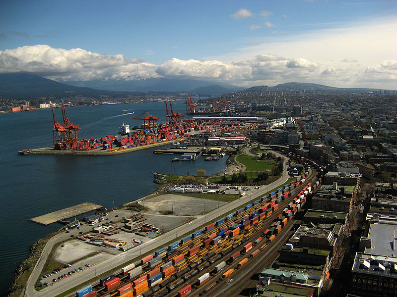 Port of Vancouver. Many cranes and shipping containers along edges of the port.