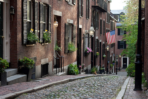 View of a cobblestone street with well maintained brick homes in Beacon Hill, Boston, MA