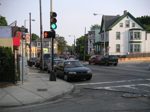 View of an intersection in Boston, Massachusetts. Run down buildings with lots of cars