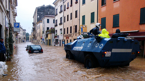Image of the flooding in a city with a car underwater in the street. Armored and raise police vehicle drive through water