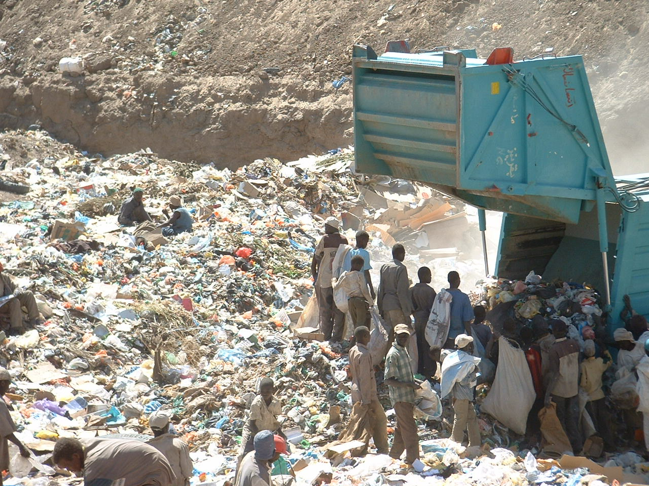 people sifting through garbage at a Sudanese landfill