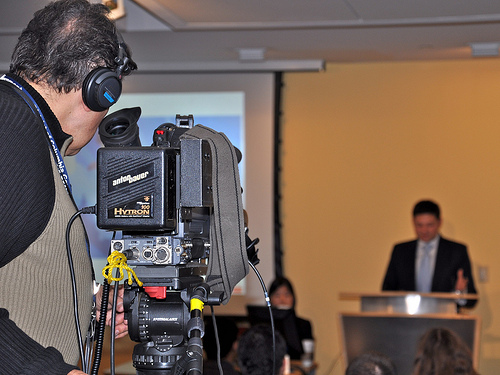 videographer filming a man speaking from a podium.