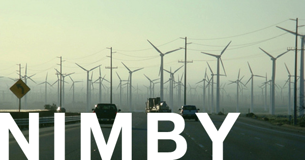Wind farm as seen from a highway with the word NIMBY written across the bottom
